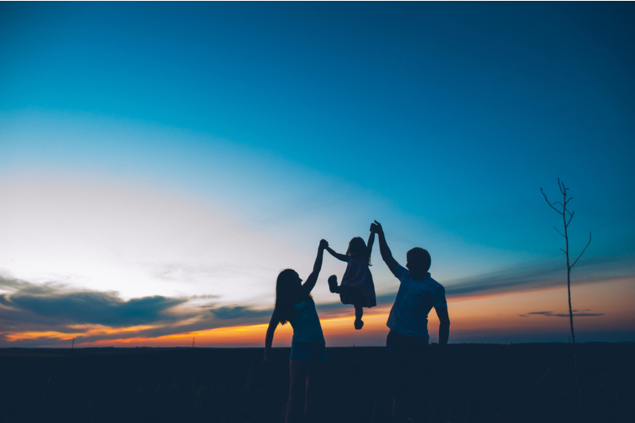 parents holding up child at sunset